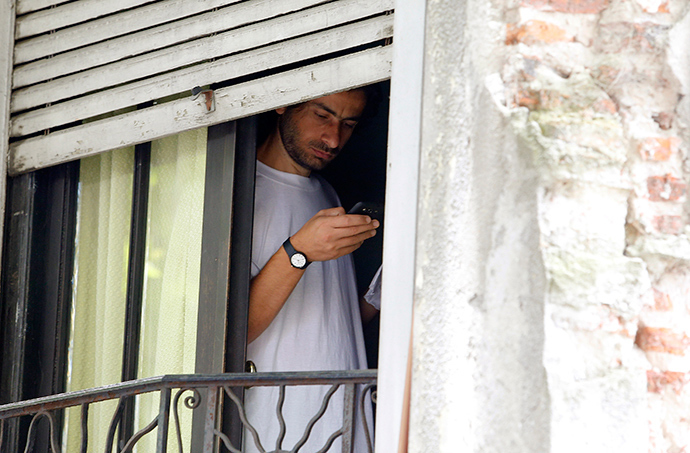 Former Guantanamo detainee Ahmed Adnan Ahjam from Syria uses a mobile phone while standing near a window in a neighbourhood in Montevideo December 12, 2014 (Reuters / Andres Stapff)