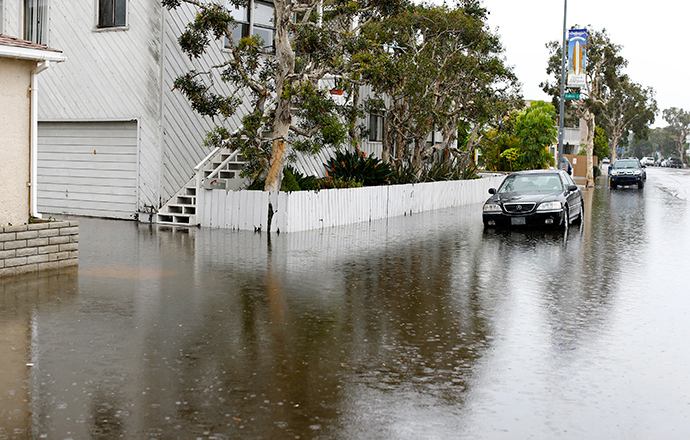 A parked automobile is surrounded by water as a winter storm brings rain and high winds to San Diego, California December 12, 2014 (Reuters / Mike Blake)