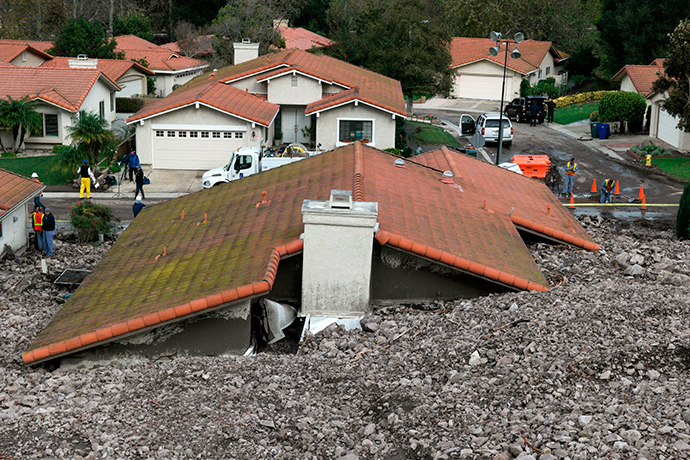 TV news crews set up across from a damaged home after a mud slide overtook at least 18 homes during heavy rains in Camarillo Springs, California December 12, 2014 (Reuters / Jonathan Alcorn)