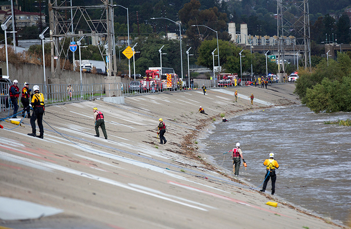Los Angeles Fire Department personnel stand by next to the Los Angeles river during a rescue operation in Los Angeles, California December 12, 2014 (Reuters / Mario Anzuoni)