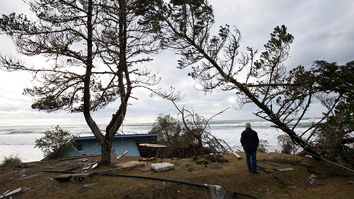 A woman watches waves roll in near a damaged house in Washaway Beach, Washington December 11, 2014 as a Pacific winter storm hits the western United States (Reuters / David Ryder)