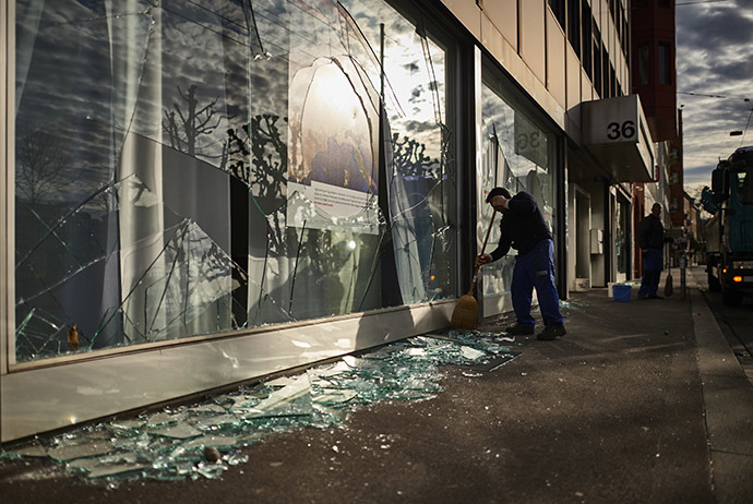 A worker cleans shattered glass outside a shop after a night of riots in Zurich on December 13, 2014. (AFP Photo/Michael Buholzer)