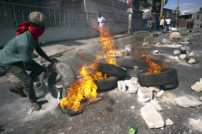 Protesters block a street with burning tires and barricades in the center of Port-au-Prince, on December 13, 2014. (AFP Photo/Hector Retamal)