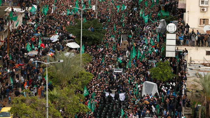 People watch as Palestinian members of al-Qassam Brigades, the armed wing of the Hamas movement, take part in a military parade marking the 27th anniversary of Hamas' founding, in Gaza City December 14, 2014. (Reuters / Suhaib Salem)