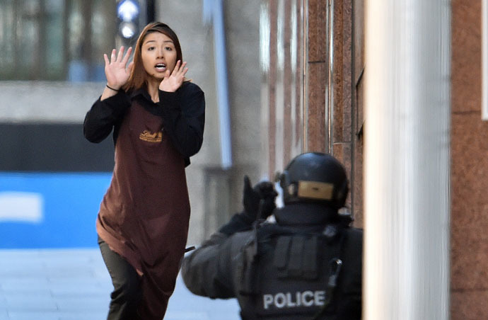 One of the hostages runs towards police from a cafe in the central business district of Sydney on December 15, 2014. (AFP Photo/Saeed Khan)
