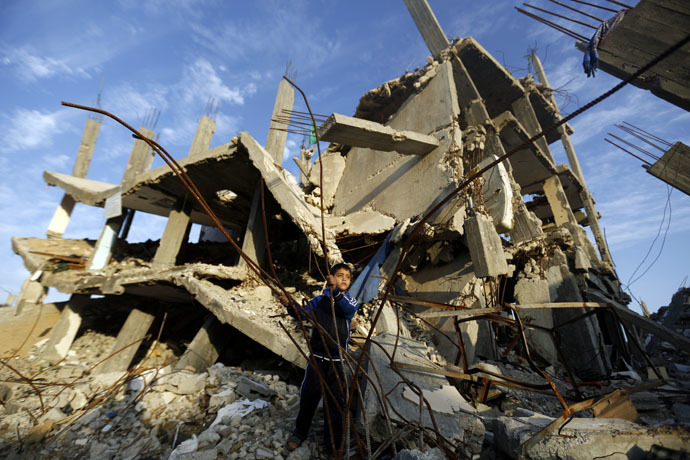 A Palestinian boy plays in the rubble of a house destroyed during the 50 days of conflict between Israel and Hamas last summer, in the Shejaiya neighborhood of Gaza City, on Decembre 11, 2014. (AFP Photo)