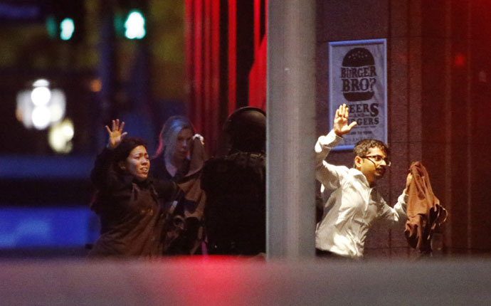Hostages run past a police officer (C) near Lindt Cafe in Martin Place in central Sydney December 16, 2014. (Reuters/Jason Reed)