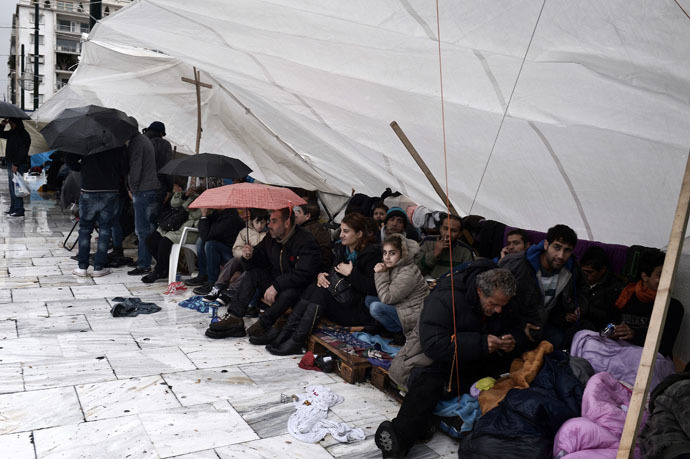 Syrian refugees sit under a makeshift tent as they take cover from the heavy rain during a protest in Athens on December 12, 2014. (AFP Photo)