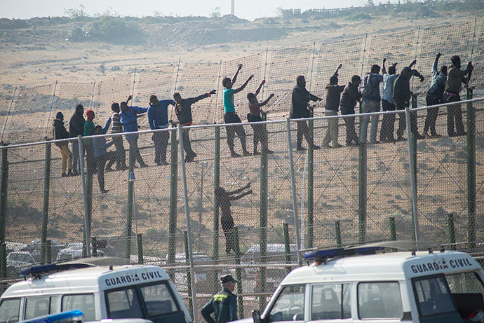 Would-be immigrants stand atop a boarder fence separating Morocco from the north African Spanish enclave of Melilla on May 1, 2014, following a morning assault on the boarder in an attempt to cross into Spain.( AFP Photo / Blasco De Aellaneda)