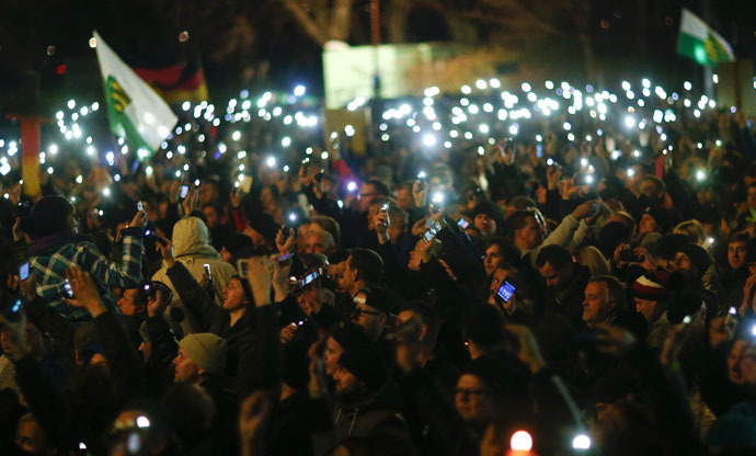 "Participants hold up their mobile phones during a demonstration called by anti-immigration group PEGIDA, a German abbreviation for ""Patriotic Europeans against the Islamization of the West"", in Dresden December 15, 2014. (Reuters)"