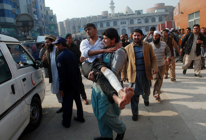 A man carries a student, who was injured during an attack by Taliban gunmen on the Army Public School, after he received treatment at a hospital in Peshawar, December 16, 2014. (Reuters/Khuram Parvez)