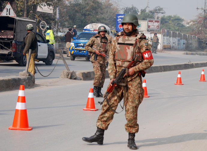 Pakistani security forces takes up positions on a road leading to the Army Public School that is under attack by Taliban gunmen in Peshawar, December 16, 2014. (Reuters/Khuram Parvez)