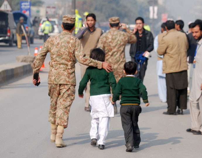 A soldier escorts schoolchildren after they were rescued from the Army Public School that is under attack by Taliban gunmen in Peshawar, December 16, 2014. (Reuters/Khuram Parvez)