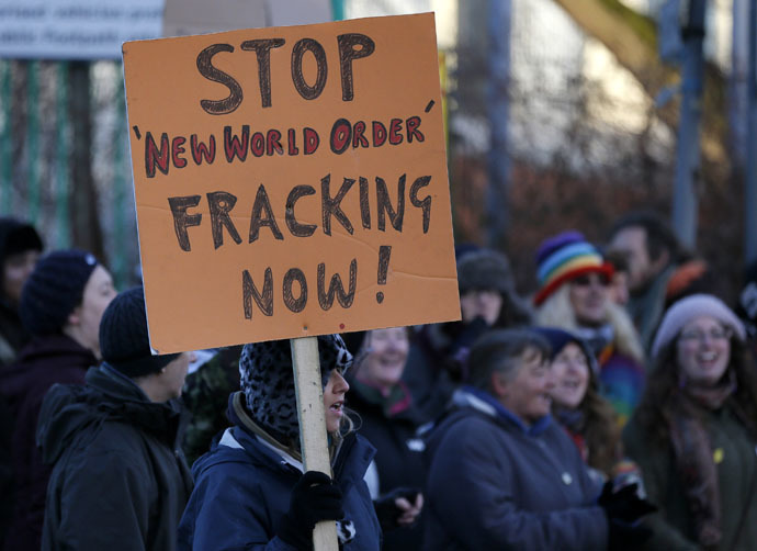 A demonstrator holds a placard in front of a police cordon outside the entrance to the IGas Energy exploratory gas drilling site at Barton Moss near Manchester in northern England January 13, 2014. (Reuters/Phil Noble)