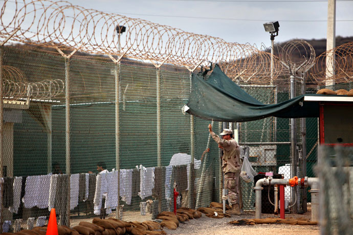 In this photo, reviewed by the US Military, a guard leans on a fence talking to a Guantanamo detainee, inside the open yard at Camp 4 detention center, at the US Naval Base, in Guantanamo Bay, Cuba, January 21, 2009. (AFP Photo)