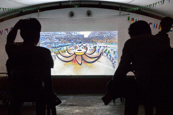 People watch a television projection of a live telecast displaying the opening ceremony of the 2014 FIFA World Cup in Brazil, on June 13, 2014 (AFP Photo)