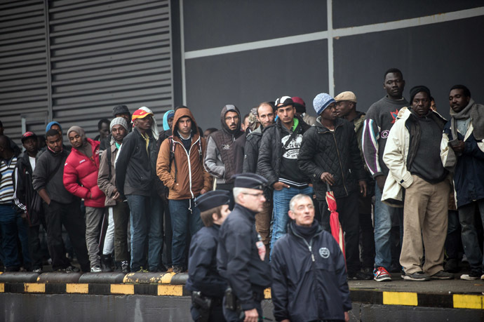 French CRS officers stand by to survey as humanitarian organizations distribute food to migrants in the northeastern French port of Calais on October 29, 2014. (AFP Photo)