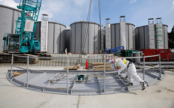 Men wearing protective suits and masks work in front of welding storage tanks for radioactive water, under construction in the J1 area at the Tokyo Electric Power Co's (TEPCO) tsunami-crippled Fukushima Daiichi nuclear power plant in Okuma in Fukushima prefecture (AFP Photo / Toru Hanai / Pool)
