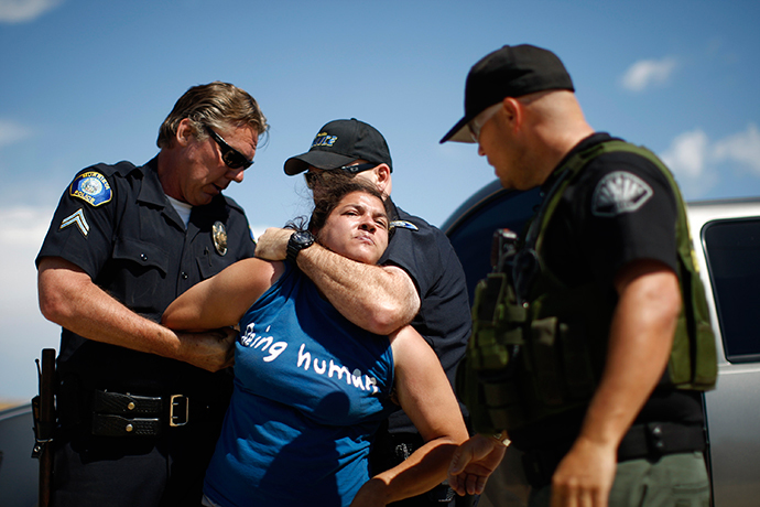 A counter-demonstrator to protesters opposing arrivals of buses carrying largely women and children undocumented migrants for processing at the Murrieta Border Patrol Station is arrested (David McNew / Getty Images / AFP)