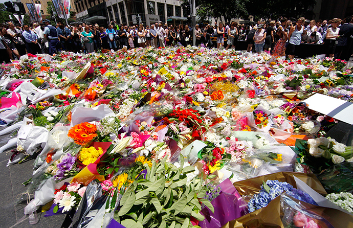 Members of the public look at thousands of floral tributes placed near the cafe in central Sydney December 16, 2014 where hostages were held for over 16-hours (Reuters / David Gray)
