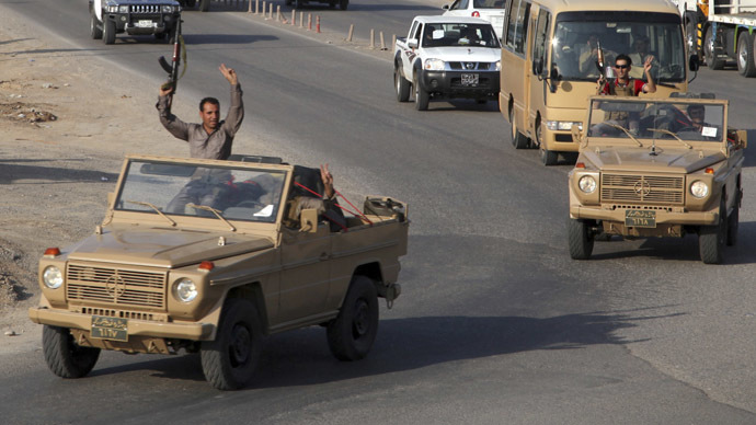 A convoy of Kurdish peshmerga fighters drive through Arbil after leaving a base in northern Iraq, on their way to the Syrian town of Kobani (Reuters)
