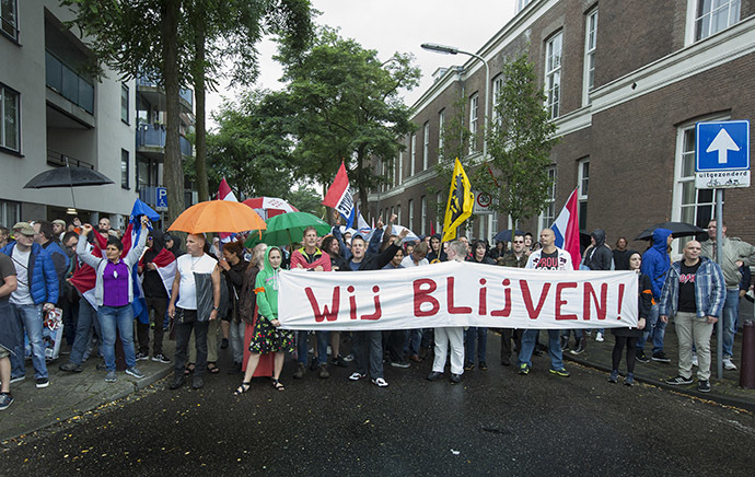 "People hold a banner reading ""We are here to stay"" during a protest against the Islamic State (IS) group and against antisemitism in The Hague, The Netherlands, on August 10, 2014. (AFP Photo/Bart Maan/Netherlands out)"
