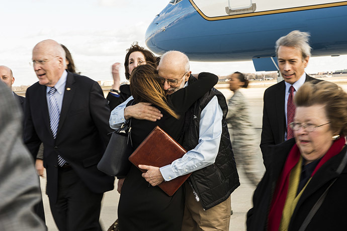 Alan Gross embraces an entourage of family and friends who were awaiting his return from five years of captivity in Cuba to Joint Base Andrews, Maryland, December 17, 2014. (Reuters/Master Sgt. Kevin Wallace/U.S. Air Force)
