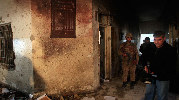 A local cameraman films in front of an army soldier at the Army Public School, which was attacked by Taliban gunmen, in Peshawar, December 17, 2014.(Reuters / Fayaz Aziz)