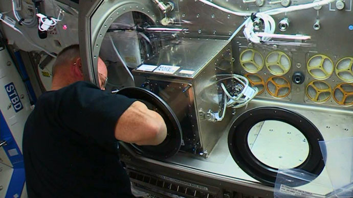 Butch reaches into the Microgravity Science Glovebox to operate the 3D printer (Image Credit: NASA)