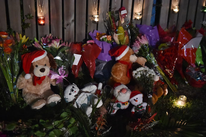 Flowers and stuffed toys are laid opposite the scene where eight children ranging from babies to teenagers were found dead in a house in the northern Australian city of Cairns early on December 20, 2014. (AFP Photo)