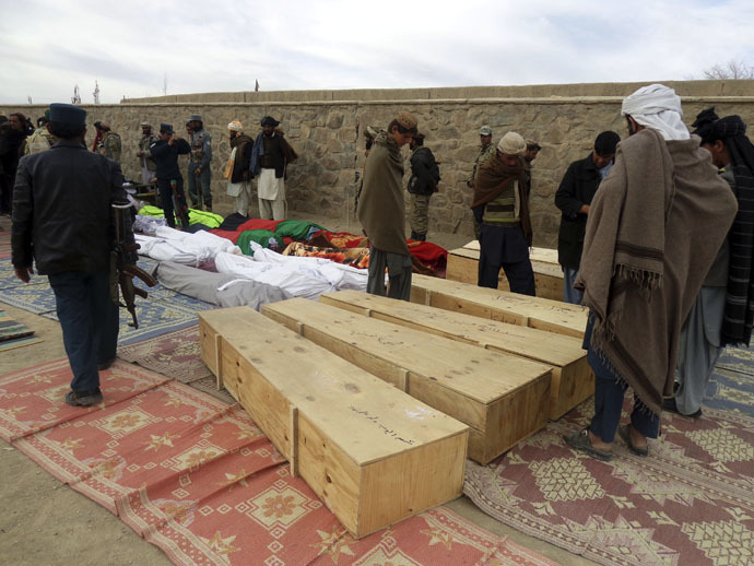 Afghan men gather around the bodies of victims of Sunday's suicide attack at a volleyball match in Yahya Khail district, Paktika province, November 24, 2014. (Reuters)