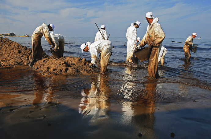 Members of the Lebanese Non-Governmental Organisation Bahr Lubnan (Lebanon's Sea) clean the oil spill at a beach in Jieh, south of Beirut, 26 October 2006. (AFP Photo / Marwan Naamani)