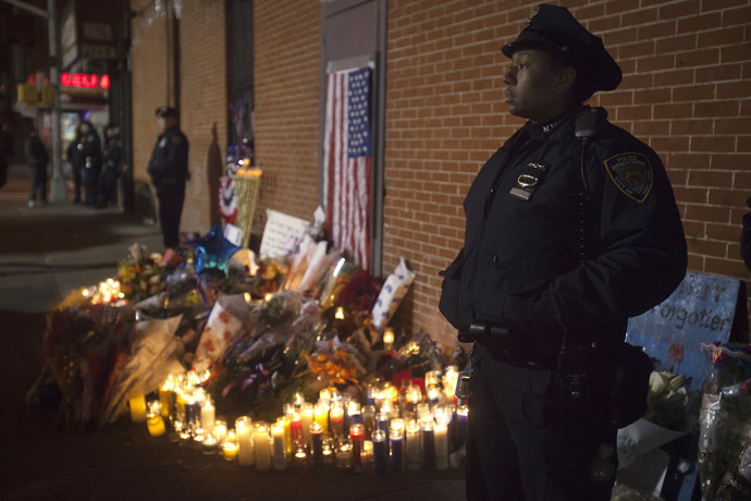 Police stand solemn during a late night vigil at a makeshift memorial at the site where two police officers were shot in the head in the Brooklyn borough of New York December 21, 2014. (Reuters/Carlo Allegri)