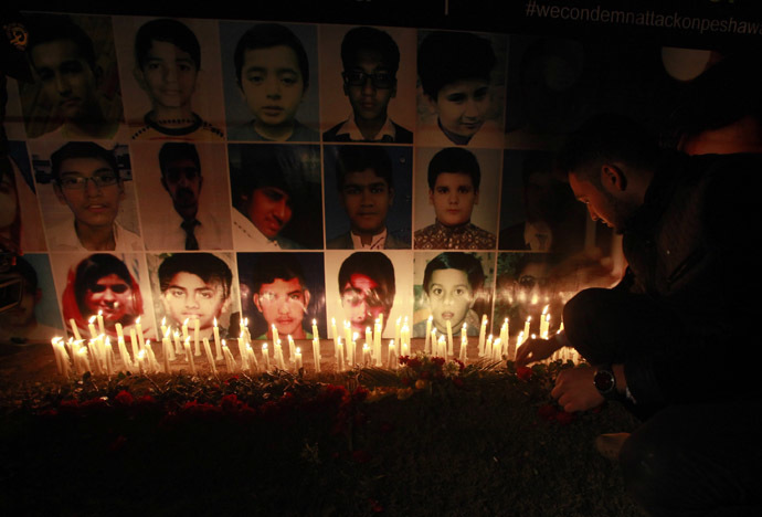 A man places a rose after lighting candles in front of portraits of the victims of the Taliban attack on the Army Public School in Peshawar, during a candlelight vigil in Lahore December 19, 2014. (Reuters/Mohsin Raza)