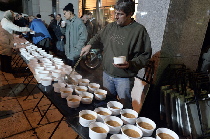A Volunteer serves a hot bean soup outside the finance ministry in Athens. (AFP Photo/Louisa Gouliamaki)