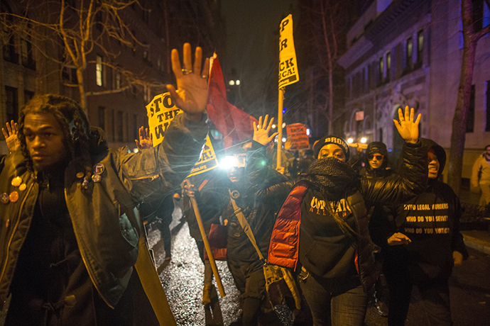 Anti-NYPD protesters march through the Upper East Side of Manhattan with their hands up in solidarity with Michael Brown on December 23, 2014 in New York City (AFP Photo / Michael Graae)