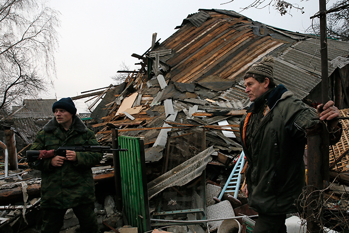 A rebel and a local citizen stand in front of a house, which according to locals was destroyed by shelling last week, in the town of Gorlovka northeast of Donetsk December 14, 2014 (Reuters / Maxim Shemetov)