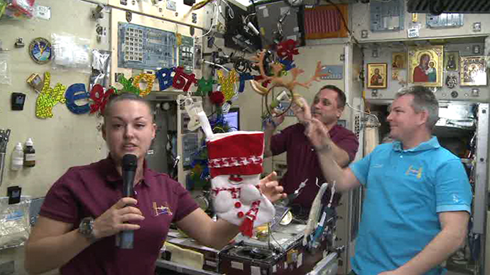 Elena Serova showing off traditional New Year symbols the ISS crew prepared for the festive celebrations: a tree, stockings and reindeer antlers' headband.