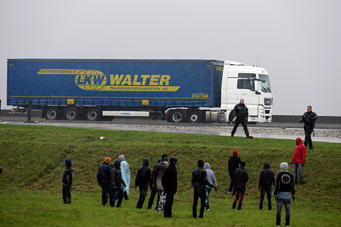 French police prevent a group of migrants from jumping onto lorries on their way to the ferry terminal in Calais (Reuters / Pascal Rossignol)