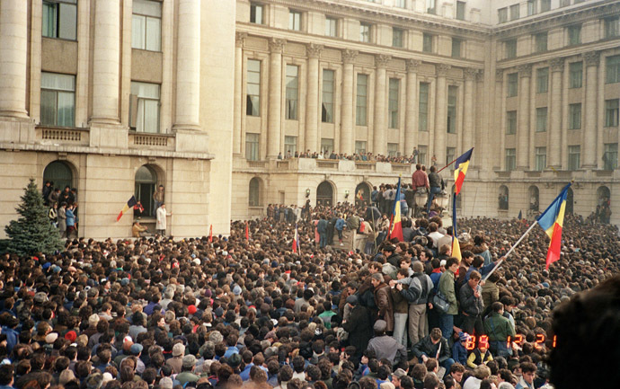 Bucharest citizens wave Romanian flags in an anti-communist demonstration on Republic Square, December 21, 1989 in front of Romanian Communist Party Central Committee HQ (background), starting a national upraising to end Nicolae Ceausescu's 24 years of dictatorial rule. (AFP Photo)