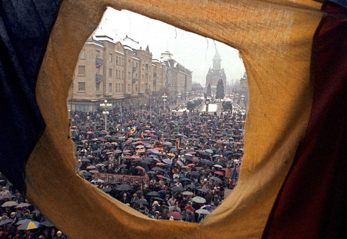 File photo of citizens, seen through a flag with the communist coat of arms torn off, demonstrating against Ceausescu in front of the Opera building December 23, 1989. (Reuters/Petar Kujundzic)