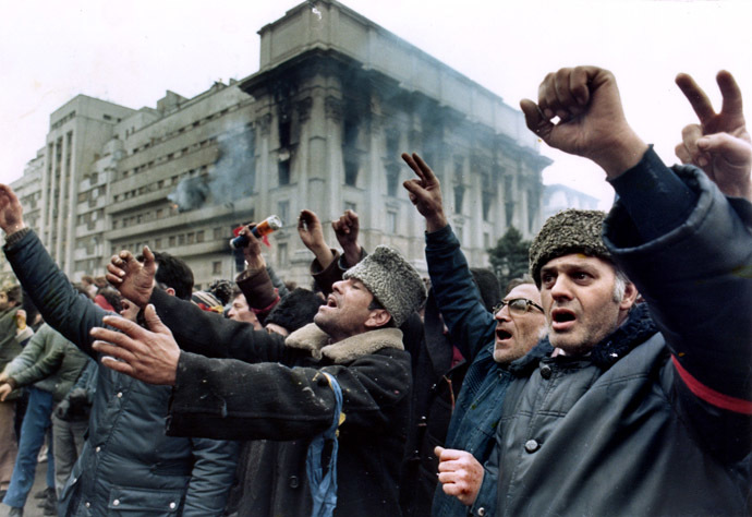 Bucharest residents demonstrate in front of a burning building at Republic Square, asking for freedom and democracy December 24, 1989. (Reuters)