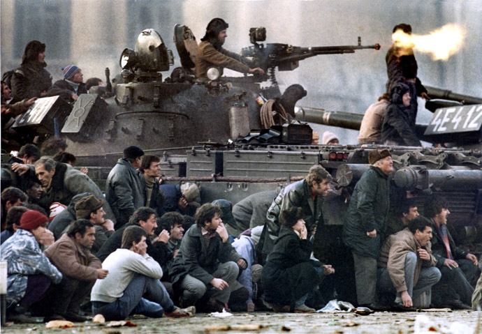 Bucharest residents protect themselves from the crossfire between an army tank and pro-Ceausescu troops during clashes in Republican Square, December 23, 1989. (Reuters)