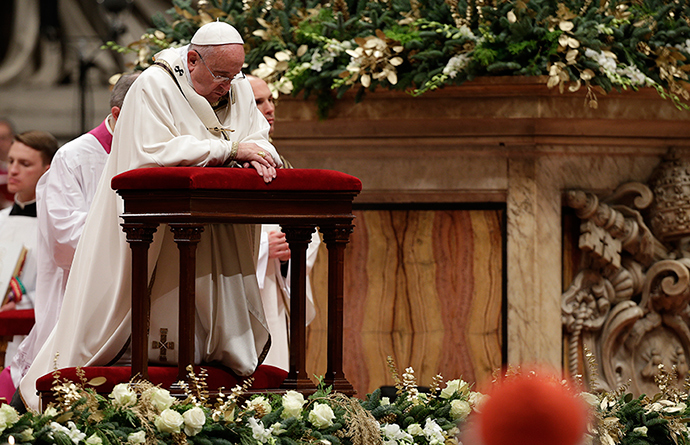 Pope Francis kneels as he leads the Christmas night mass in Saint Peter's Basilica at the Vatican December 24, 2014 (Reuters / Max Rossi)