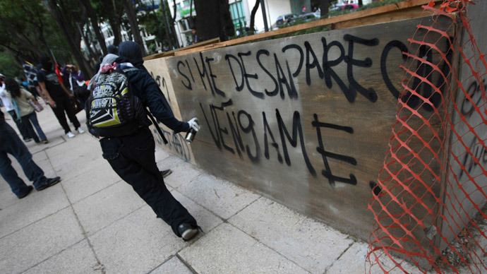 An activist sprays graffiti during a march to demand justice for the 43 missing students from Ayotzinapa Teacher Training in Mexico City December 26, 2014. (Reuters / Bernardo Montoya)