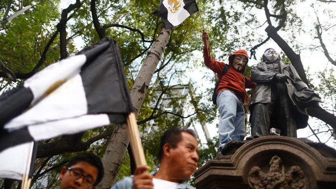An activist wearing a Guy Fawkes mask is seen on a monument during a march to demand justice for the 43 missing students from Ayotzinapa Teacher Training in Mexico City December 26, 2014. (Reuters / Edgard Garrido)