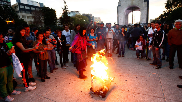 Activists burn a figure of President Enrique Pena Nieto during a march to demand justice for the 43 missing students from Ayotzinapa Teacher Training at Revolucion monument in Mexico City December 26, 2014.(Reuters / Edgard Garrido)