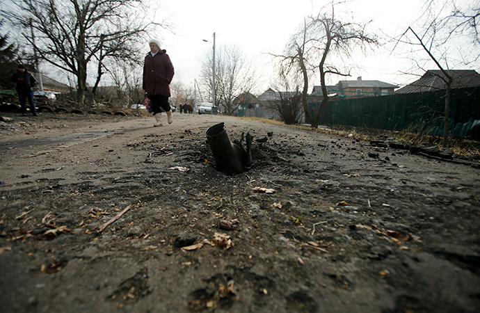 A woman walks next to an exploded shell in Krasnyi Pakhar village near Donetsk, eastern Ukraine (Reuters / Antonio Bronic)