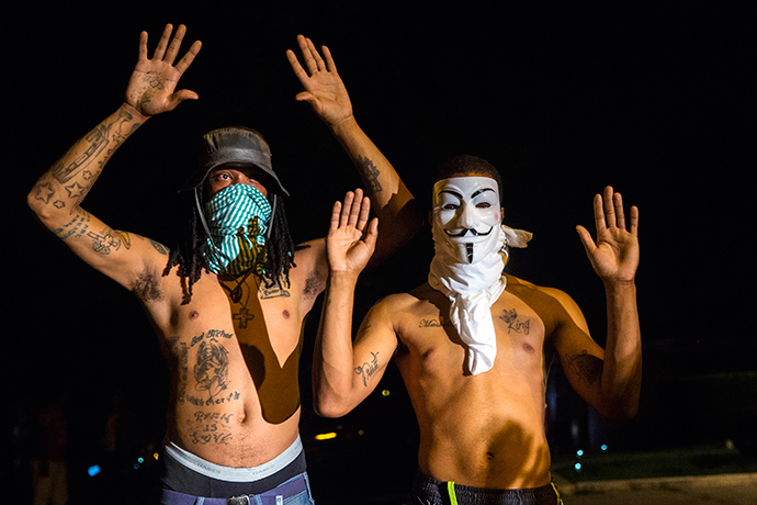 Members of a rowdy group of demonstrators stand with their hands up as they are lit by a police spotlight on West Florissant during protests in reaction to the shooting of Michael Brown near Ferguson, Missouri August 18, 2014. (Reuters / Lucas Jackson)