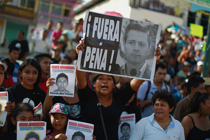 A woman holds a sign during a protest demanding justice for the 43 missing students of the Ayotzinapa Teacher Training College Raul Isidro Burgos, in Tecoanapa, in the southern Mexican state of Guerrero, December 11, 2014. (Reuters / Jorge Dan Lopez)